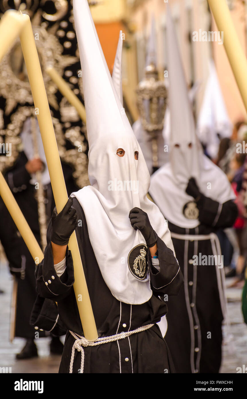 Hooded penitent looks contemplative during Semana Santa Processions Cadiz City Spain - Stock Image