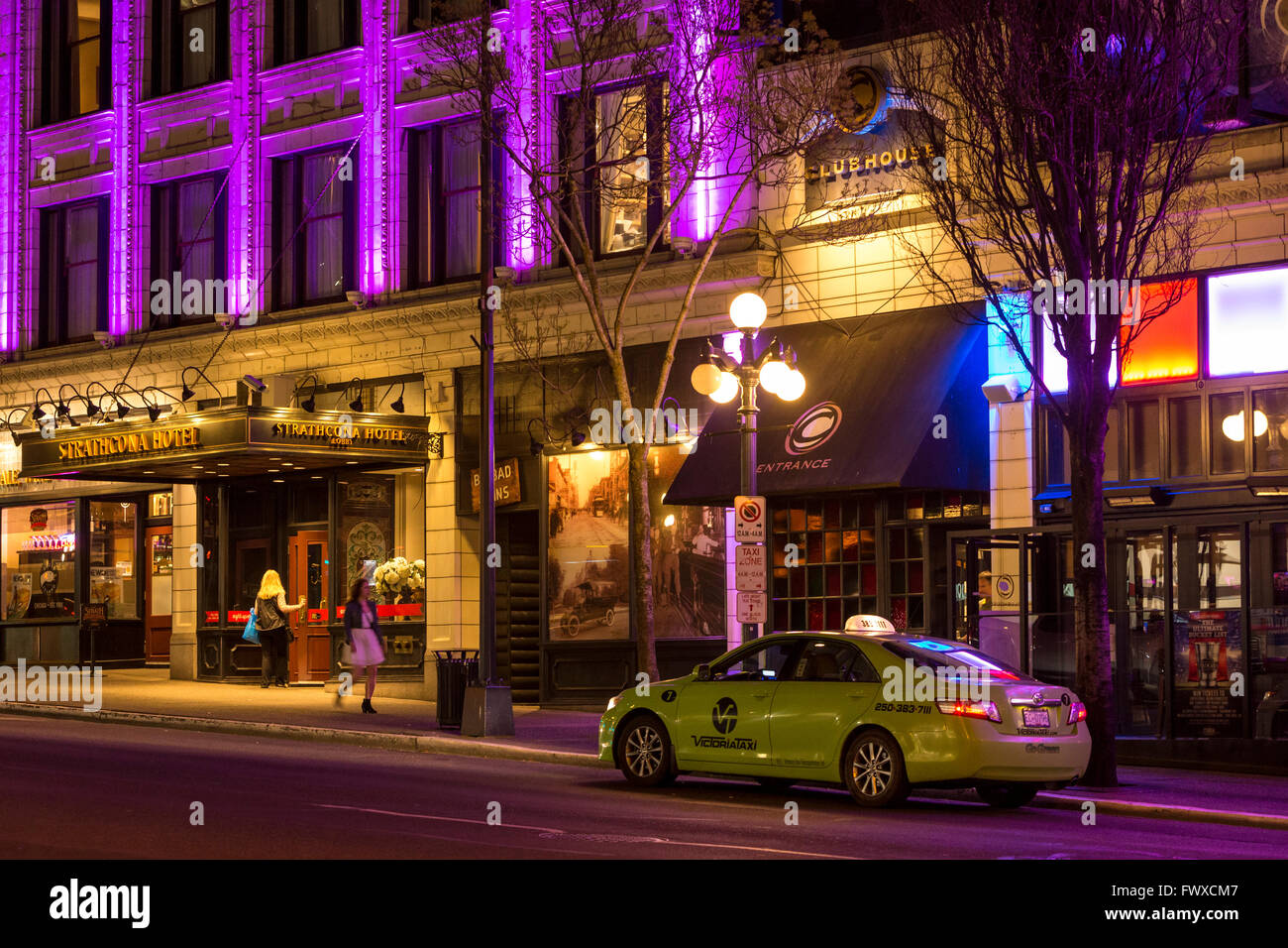 Taxicab waiting for customer outside Strathcona hotel and pub with women on street at night -Victoria, British Columbia, - Stock Image
