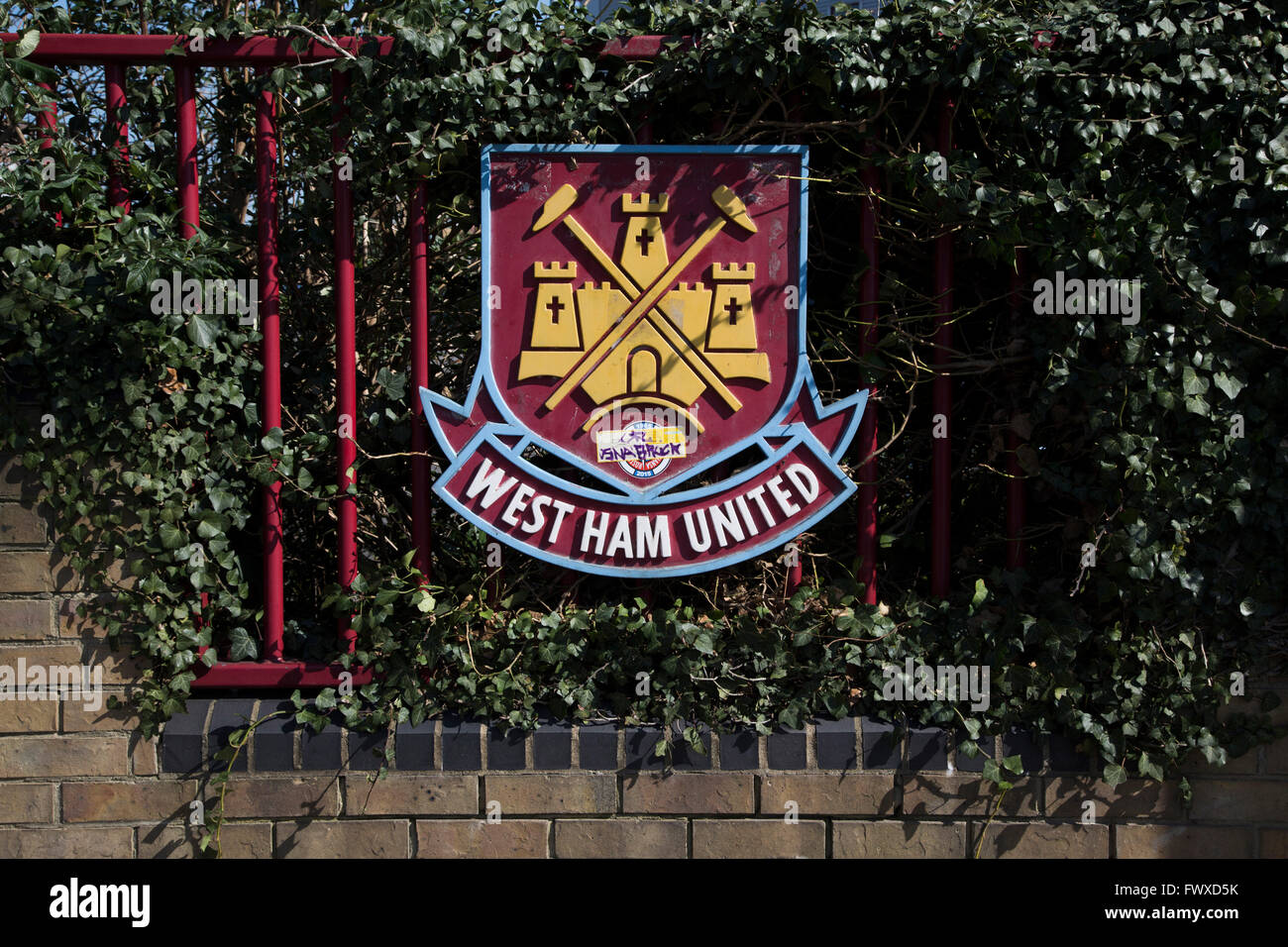 A club crest on railings at the entrance to the Boleyn Ground, pictured before West Ham United hosted Crystal Palace - Stock Image