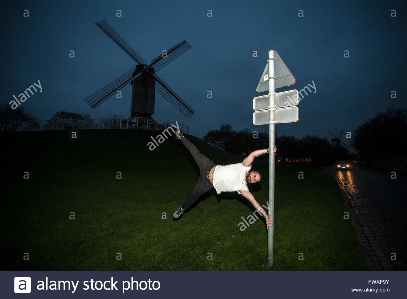 Traceur practicing parkour. Man imitating Sint-Janshuismolen windmill on  street sign, Windmills of Bruges  © - Stock Image