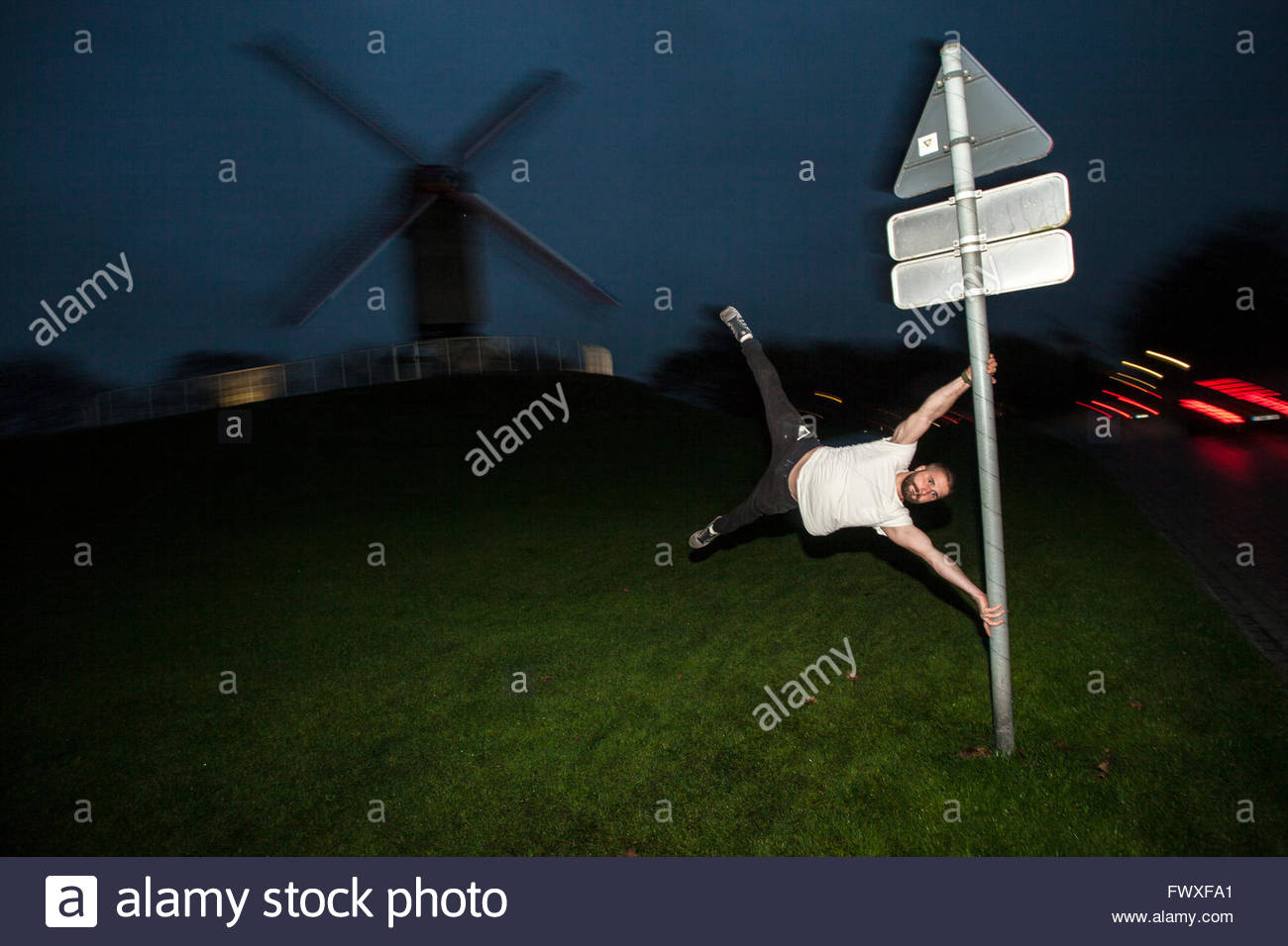 Traceur practicing parkour. Man imitating Sint-Janshuismolen windmill on a street sign, Windmills of Bruges © - Stock Image
