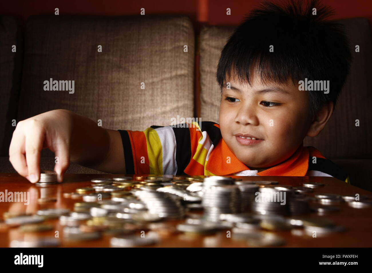 Young Boy Stacking or Piling Coins - Stock Image