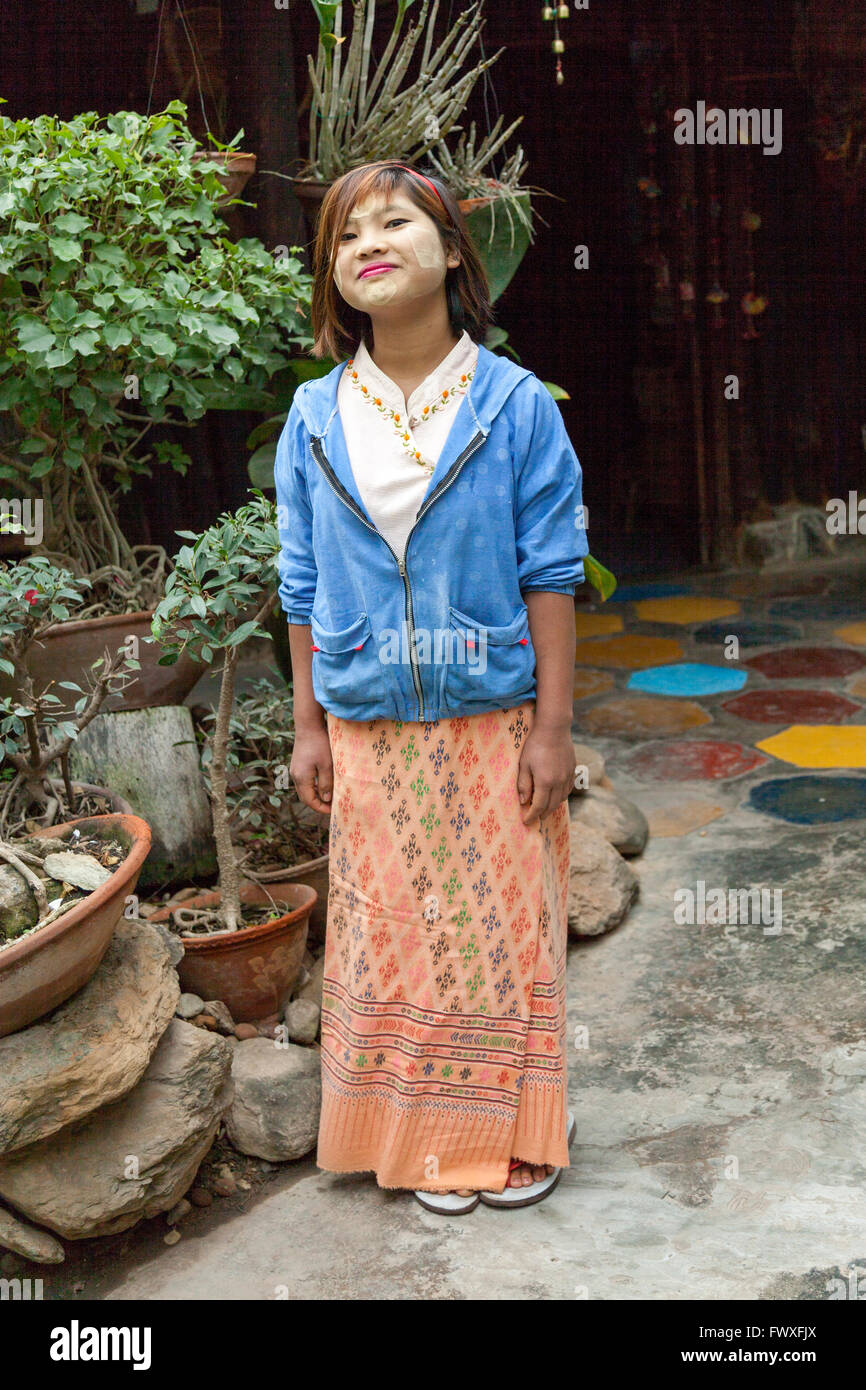 Young girl having made herself up with thanaka (Nyaungshwe). This plant powder is now used by City Burmese women Stock Photo