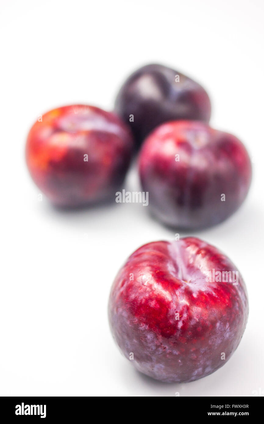 Four fresh plum placed on the white table - Stock Image