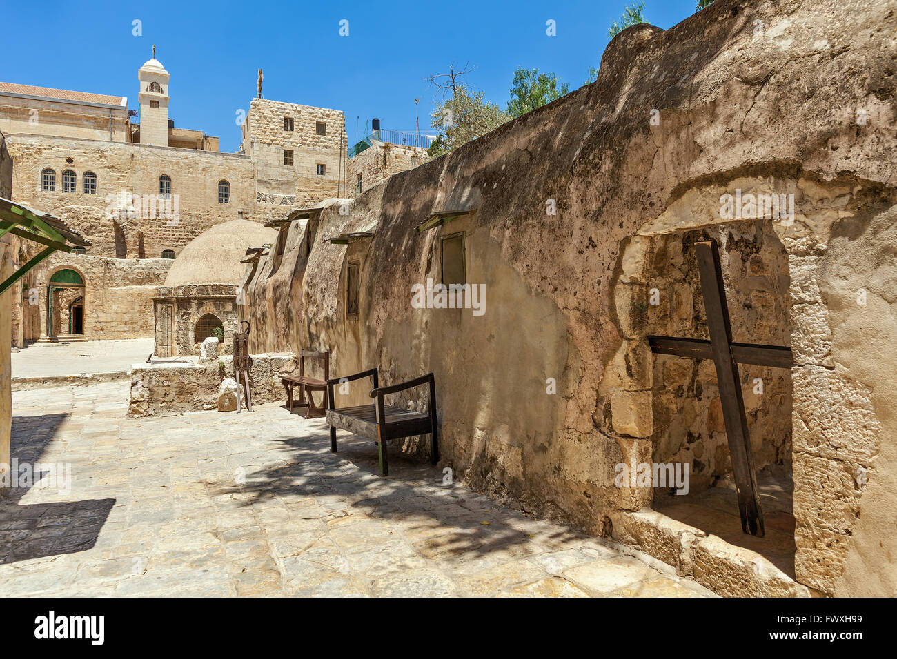 Wooden cross and stone monastic cells on the roof of the Church of the Holy Sepulchre in Jerusalem, Israel. - Stock Image