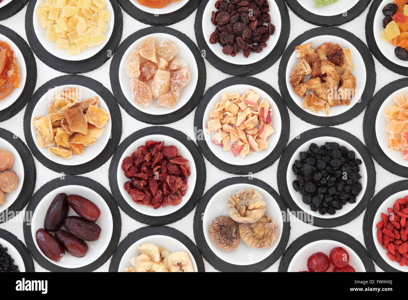 Dried fruit selection in porcelain bowls on slate rounds over white background. - Stock Image