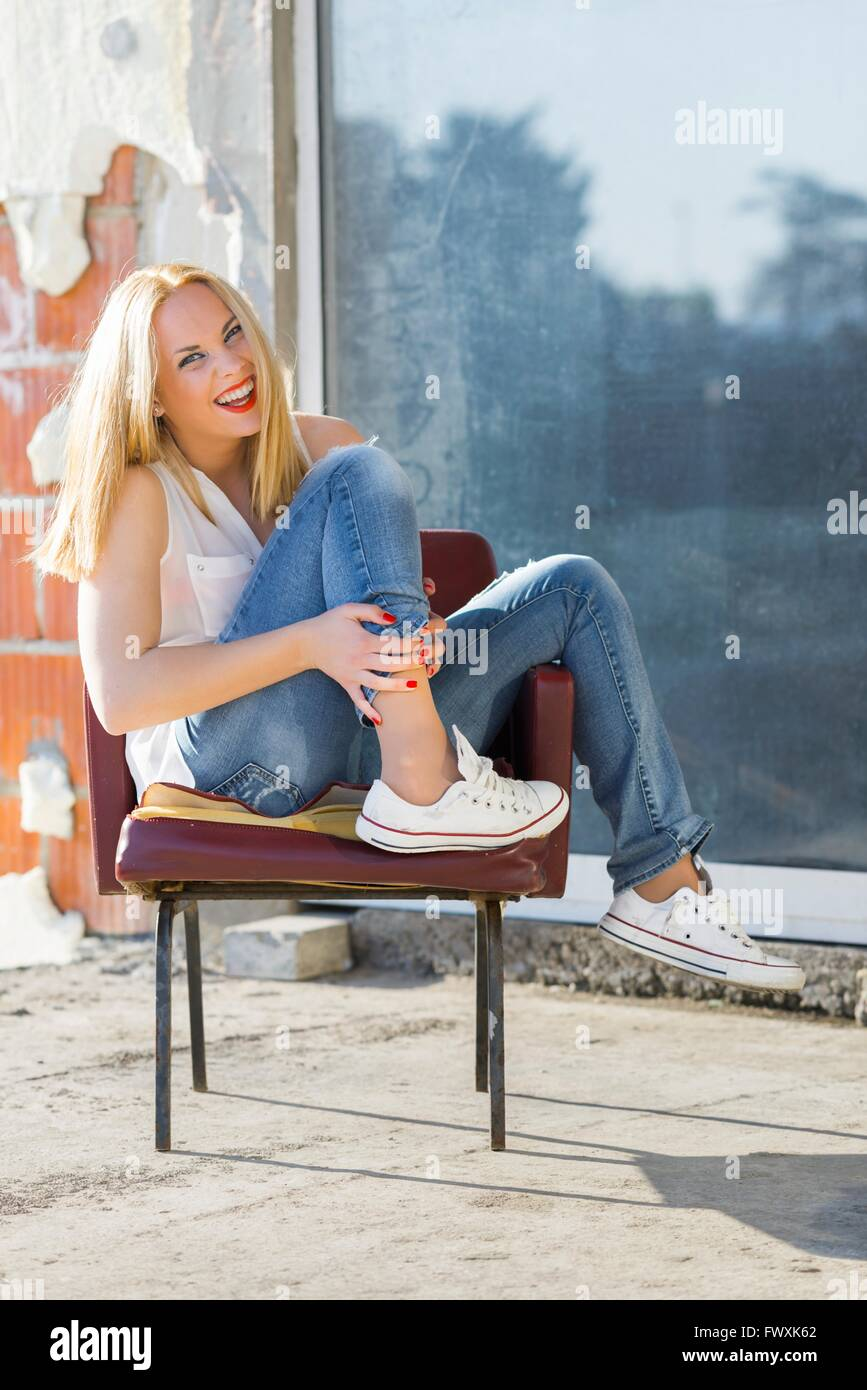 Girl next door denims sneakers leg on chair tucked laughing at camera outdoors loud chirp yell ordinary people attractive - Stock Image