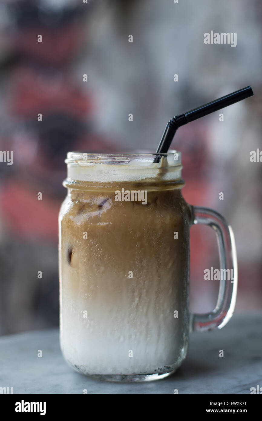 Iced coffee with milk and straw - Stock Image