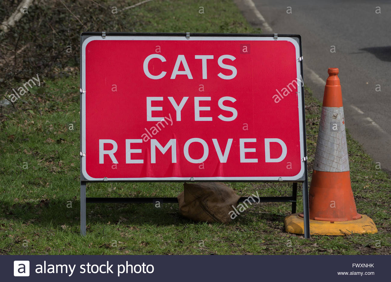 Ambiguous traffic sign warning motorists that the reflective 'cat's eyes' have been removed from a stretch - Stock Image