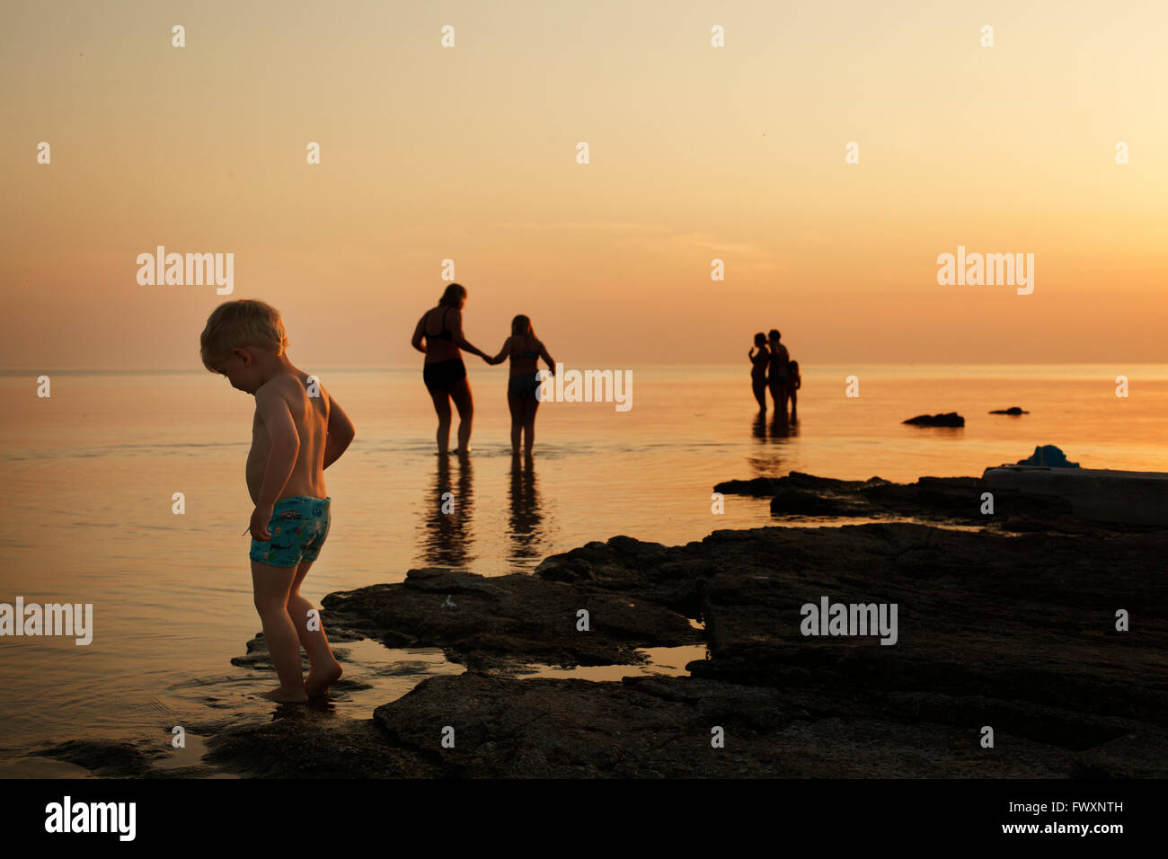 Sweden, Gotland, Faro, Boy (2-3) with family on beach at dusk - Stock Image