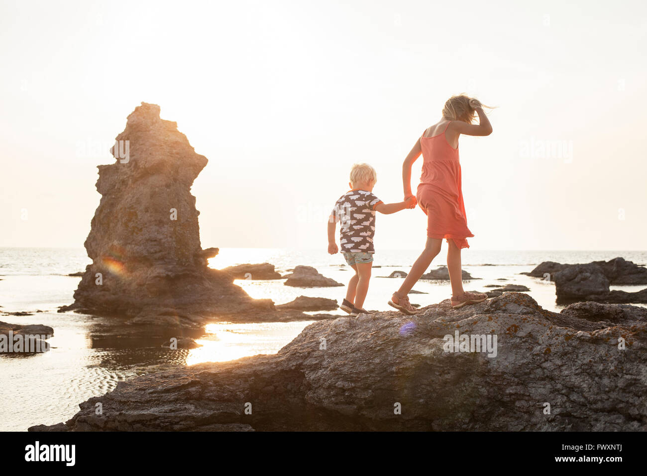 Sweden, Gotland, Faro, Gamle hamn, Girl (8-9) walking with brother (2-3) on coastal rocks Stock Photo