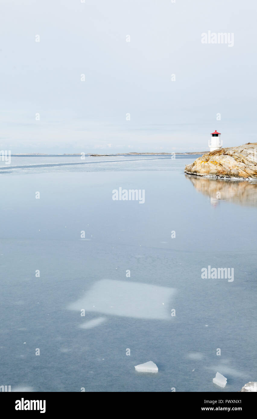 Sweden, Bohuslan, Orust, Mollosund, Lighthouse by frozen sea - Stock Image