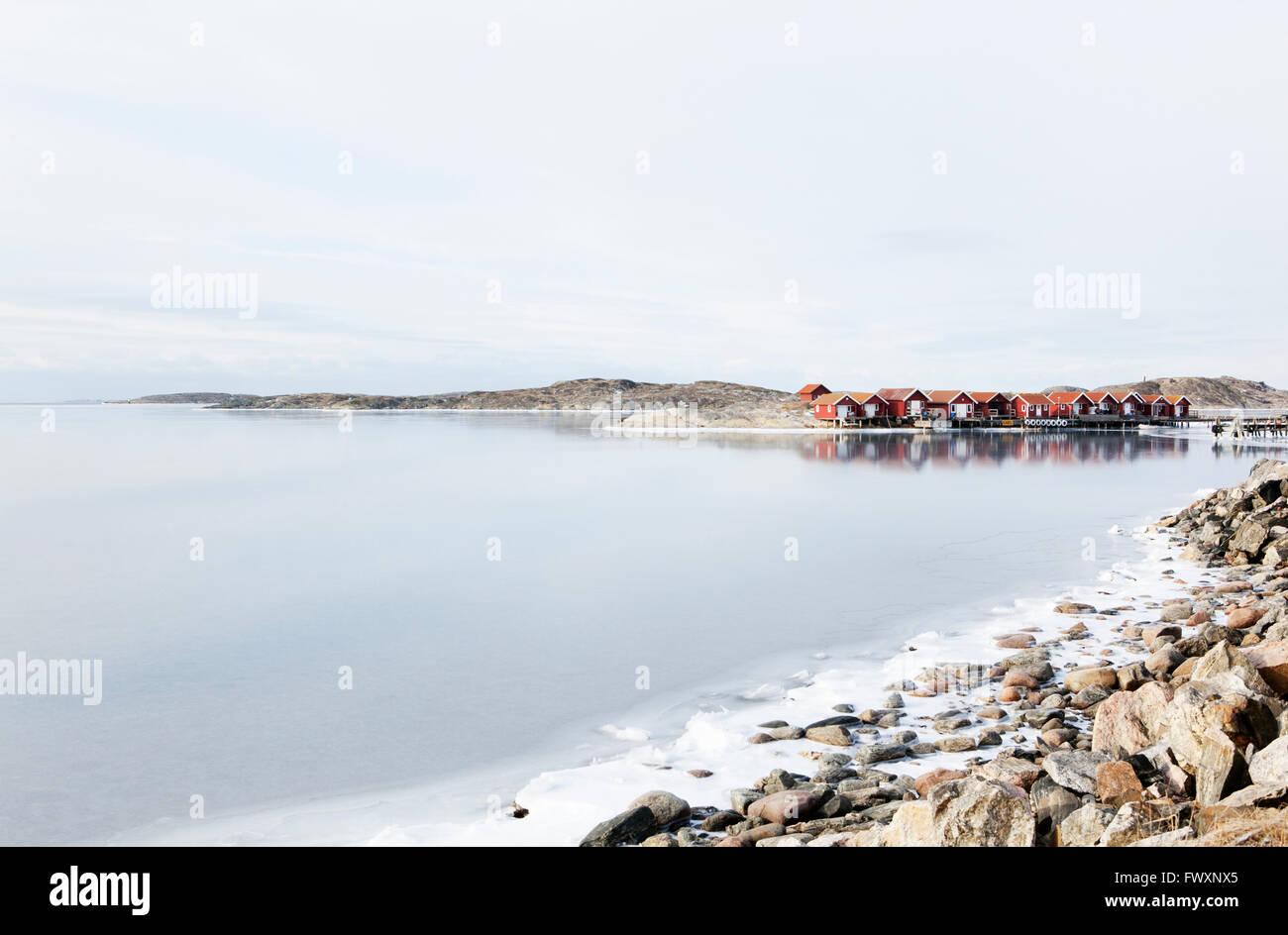 Sweden, Bohuslan, Orust, Edshultshall, Wooden houses and rocky coastline in winter Stock Photo