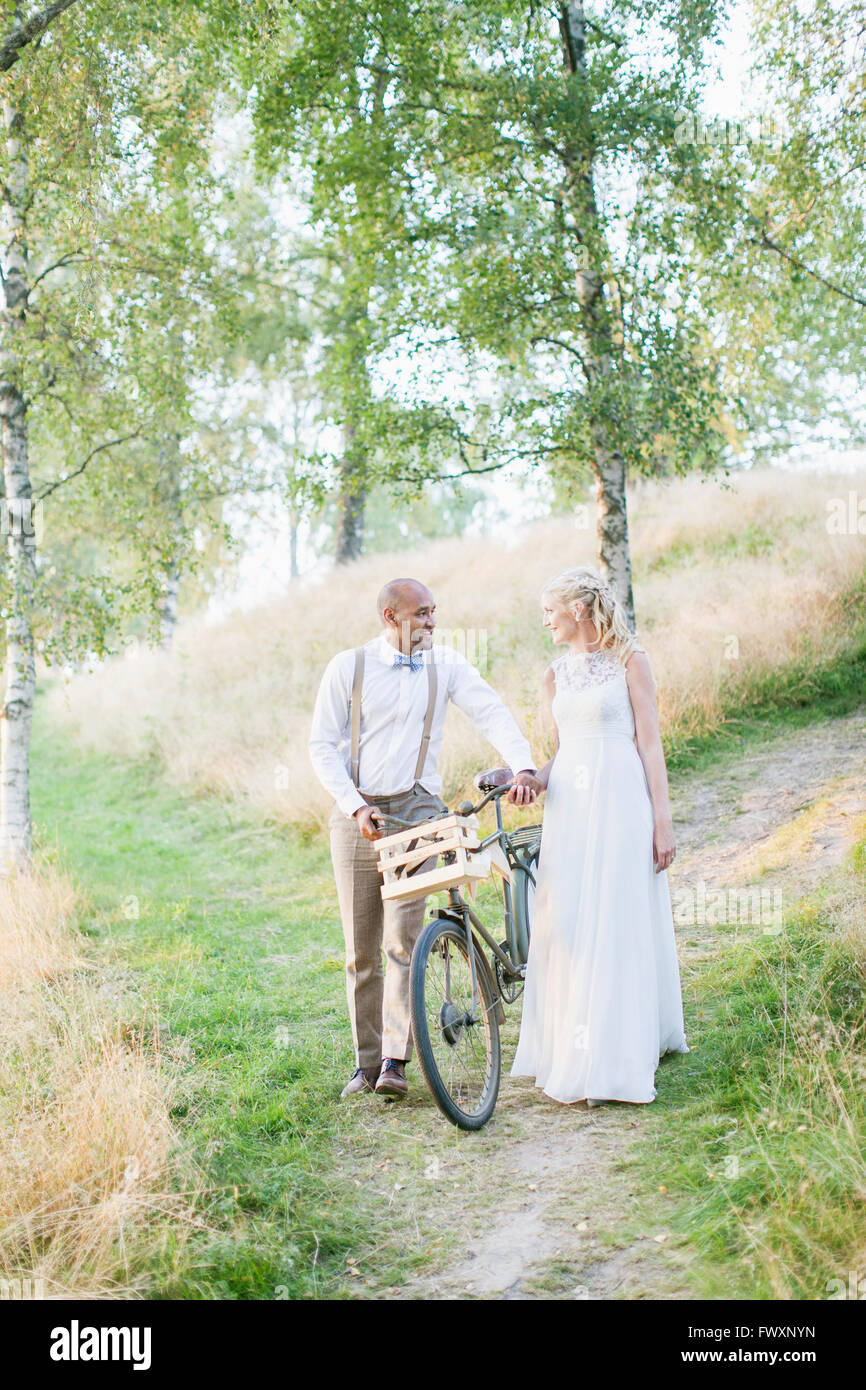 Sweden, Smaland, Mullsjo, Newly wed couple with bicycle on trail - Stock Image