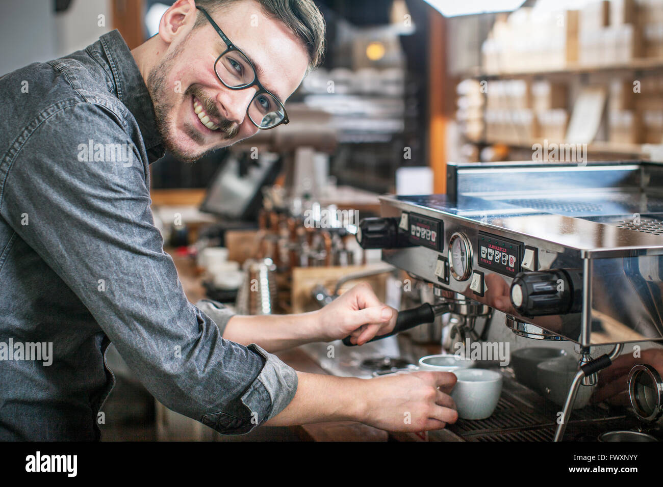 Sweden, Smiling barista making coffee - Stock Image