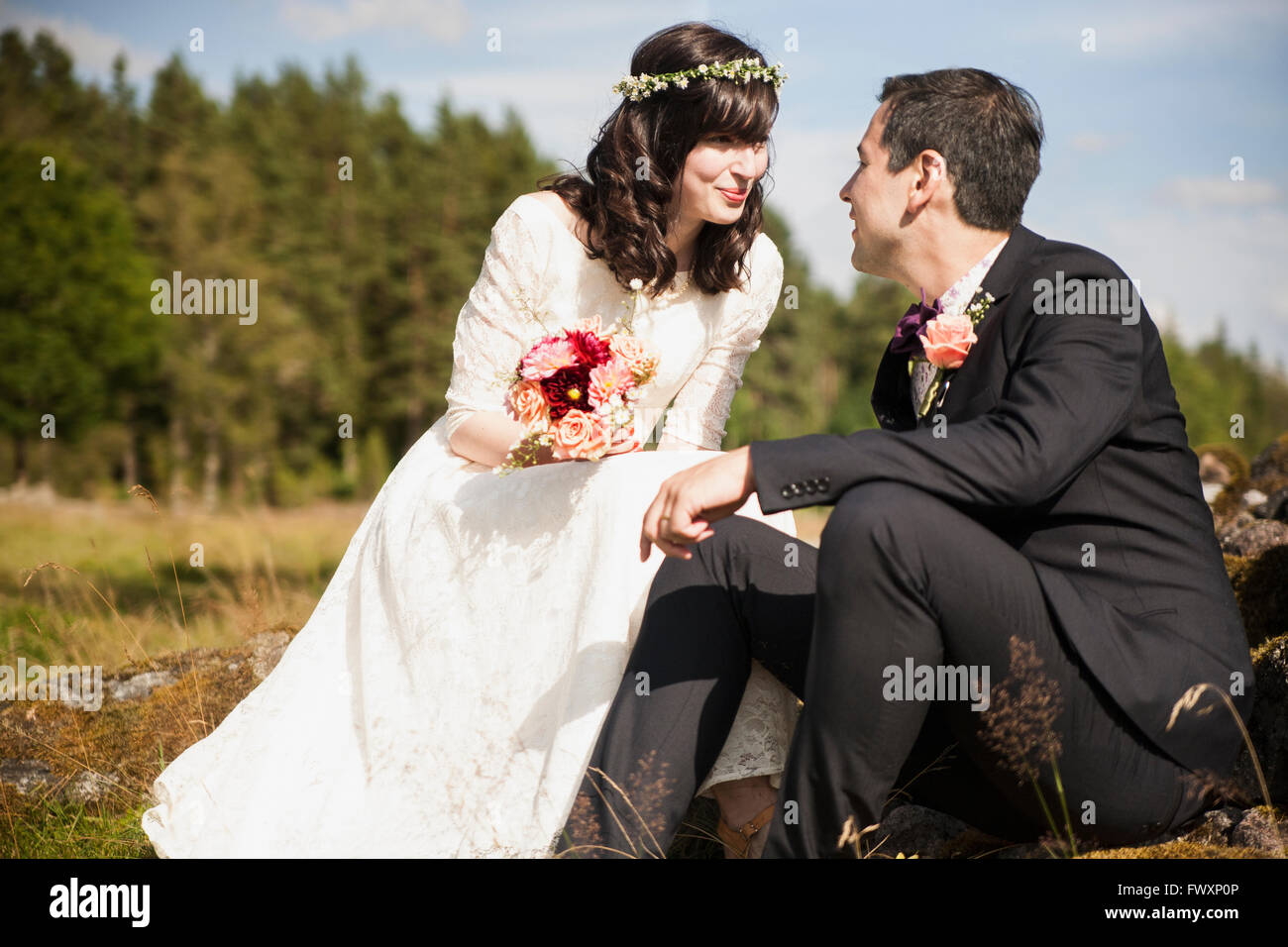Sweden, Smaland, Vetlanda, Holsbybrunn, Newlyweds face to face in field - Stock Image