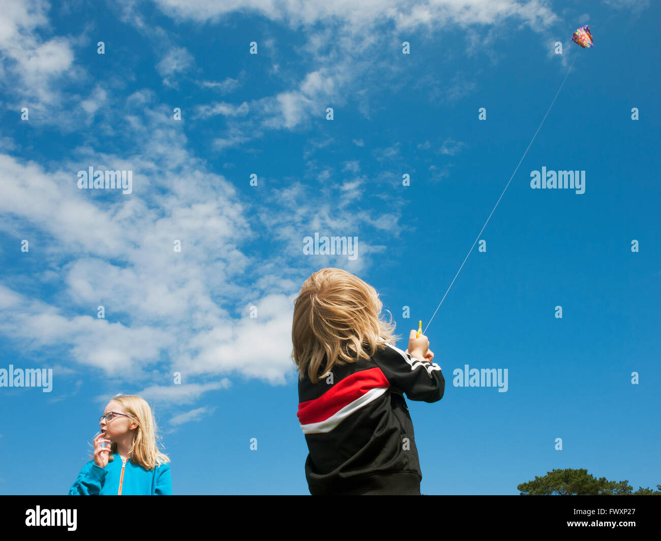 Sweden, Skane, Nyhamnslage, Two sisters (6-7, 10-11) flying kite - Stock Image
