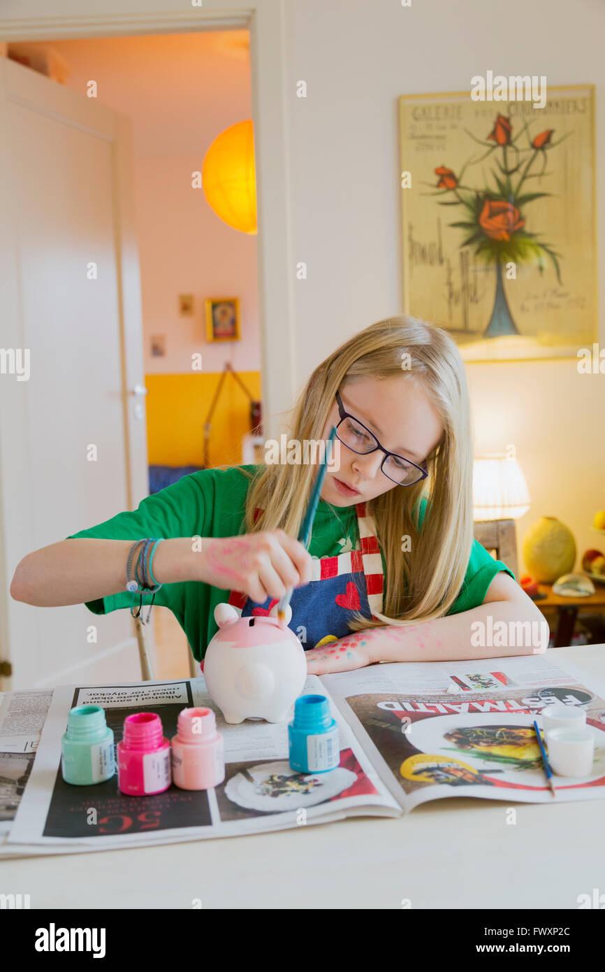 Girl (10-11) painting artwork - Stock Image
