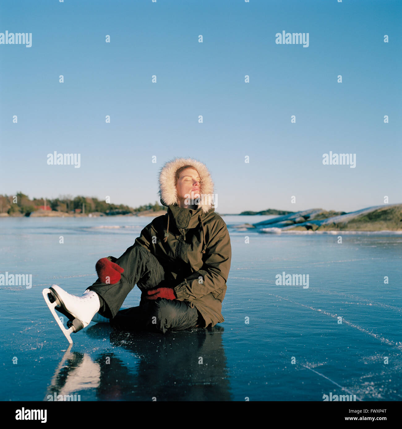 Sweden, Uppland, Varmdo, Bjorno, Mid adult woman sitting on frozen lake - Stock Image