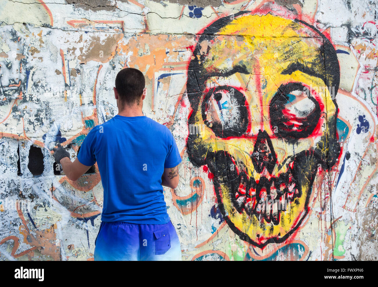Graffiti artist spraying over old graffiti on wall in Spain - Stock Image