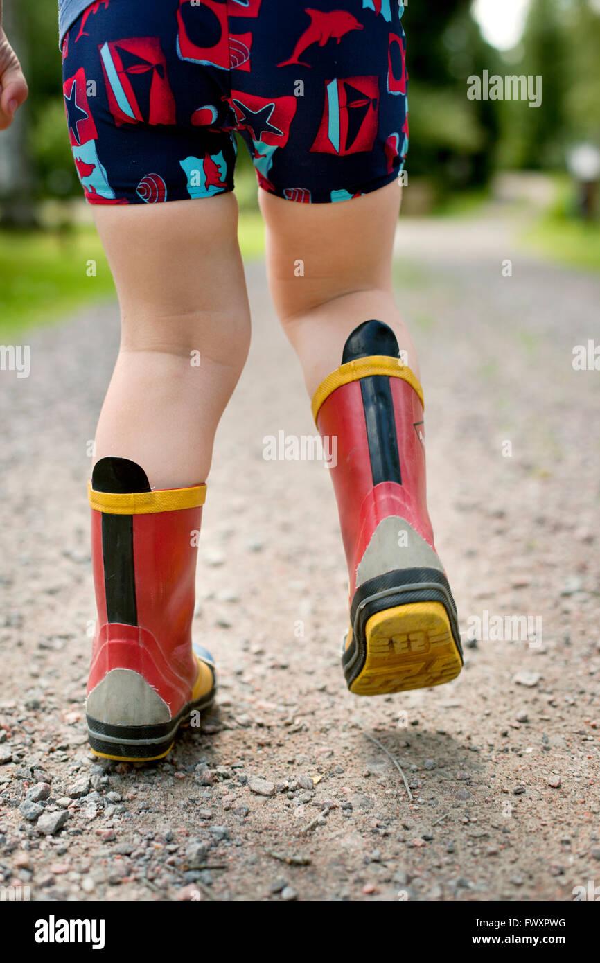 Sweden, Little boy (2-3) walking in rubber boots Stock Photo
