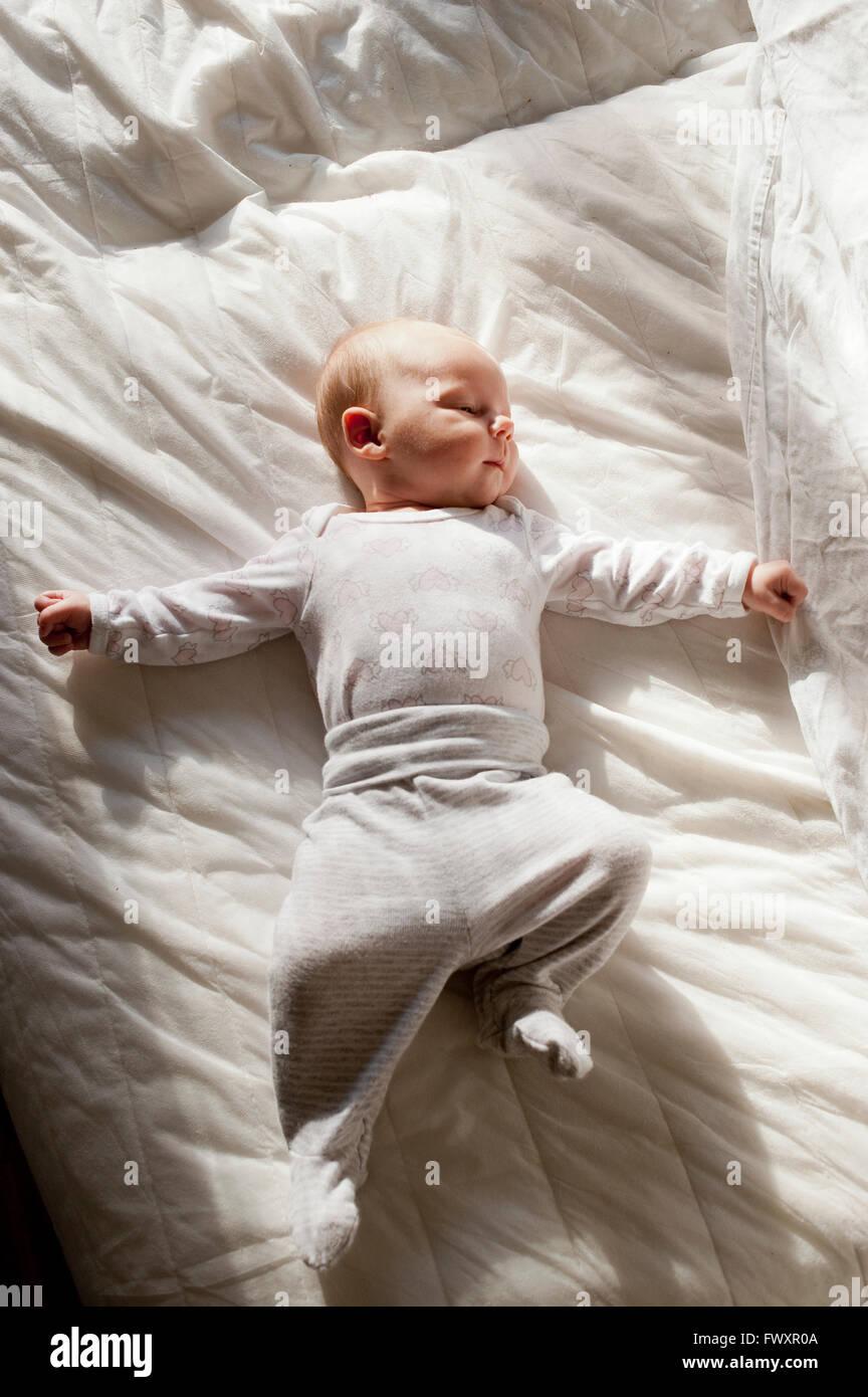 Sweden, Baby girl (2-5 months) lying down on duvet - Stock Image