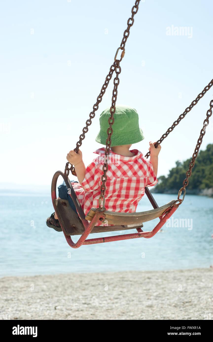 Greece, Skopolos, Boy (4-5) in green sun hat sitting on swing - Stock Image