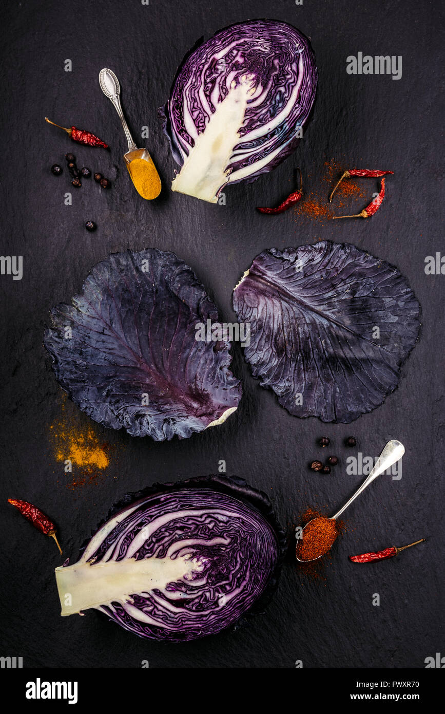 Slices of purple cabbage with red and orange spices on a black background - Stock Image