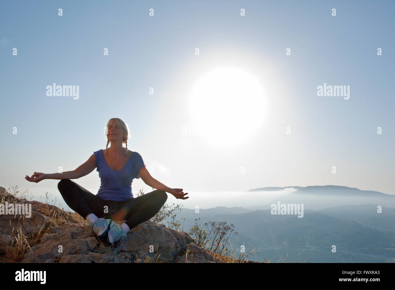 Spain, Alicante, Cocentaina, Mature woman sitting cross-legged on rocks and meditating - Stock Image