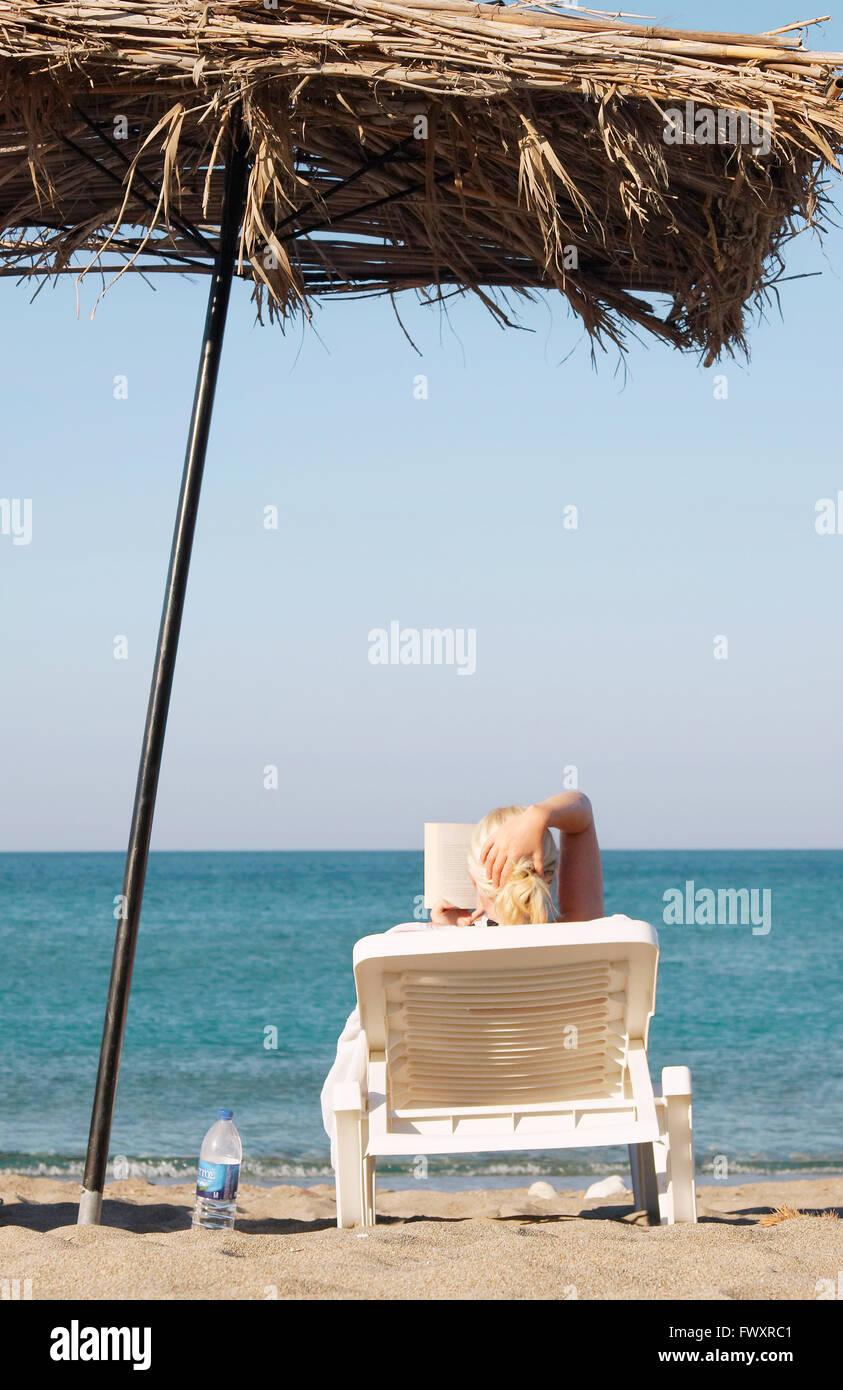 Greece, Karpathos, Woman sunbathing and reading book at beach Stock Photo