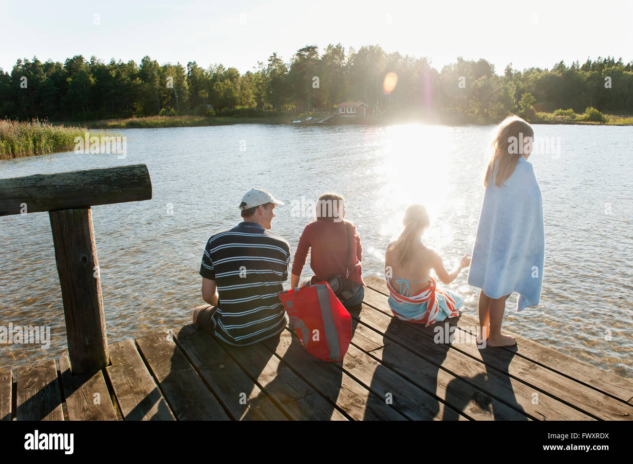 Sweden, Vastra Gotaland, Kallandso, Family with two children (6-7, 12-13) on pier - Stock Image