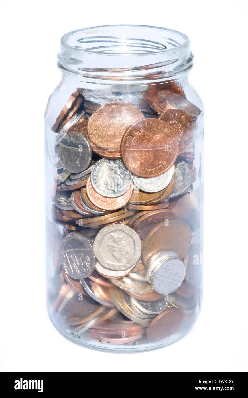 Savings jar full of coins, UK. - Stock Image