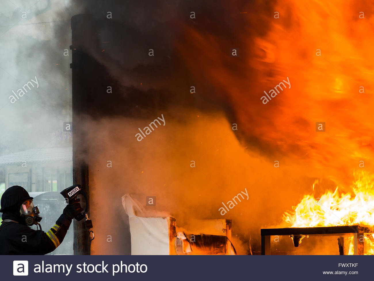 Sweden, Sodermanland, Firefighter using thermal imaging camera standing by fire - Stock Image