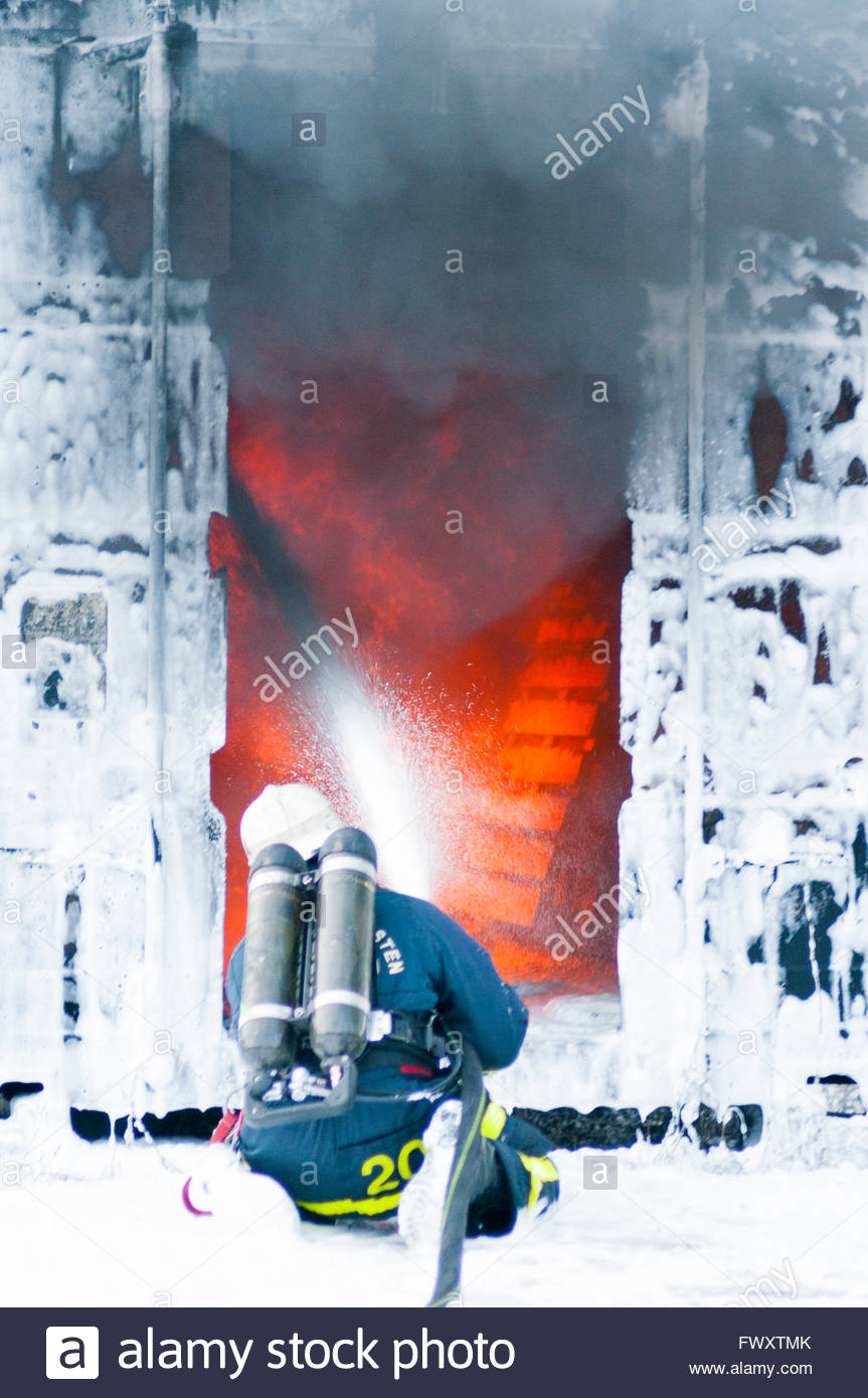 Sweden, Sodermanland, Firefighter spraying foam to stop fire - Stock Image