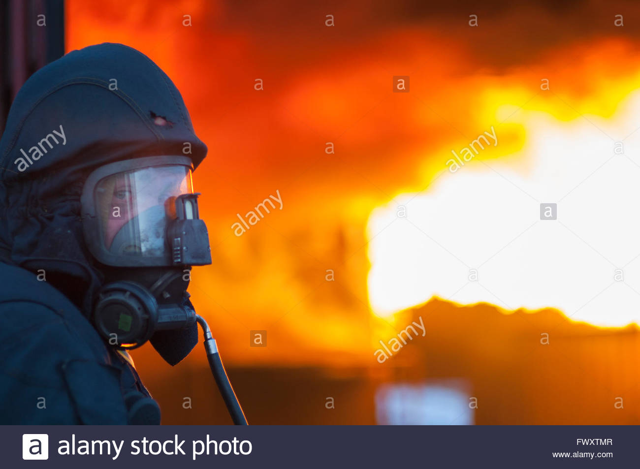 Sweden, Sodermanland, Firefighter wearing protective mask with fire burning in background - Stock Image