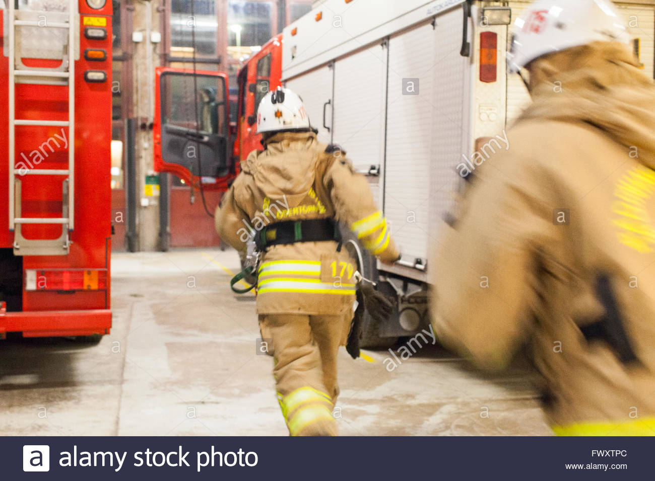 Firefighter running towards fire engine - Stock Image