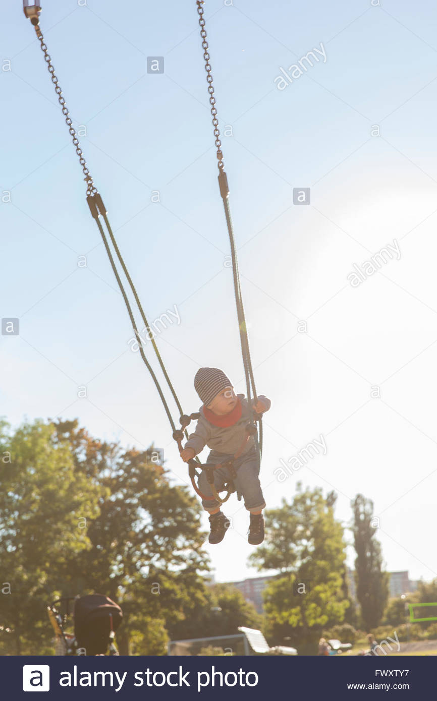 Sweden, Stockholm, Boy (12-17 months) swinging outdoors Stock Photo