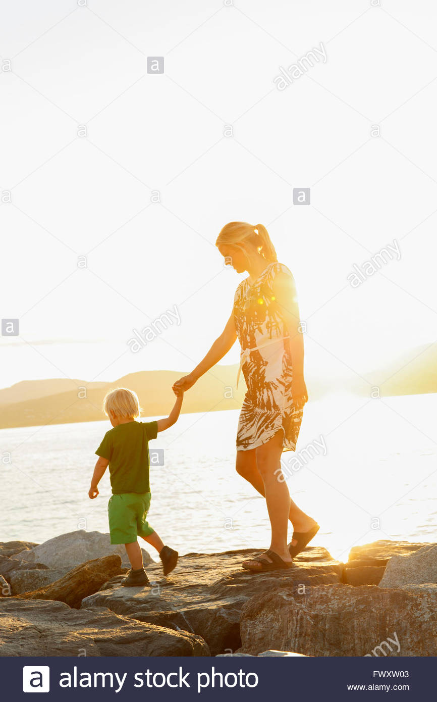 France, Provence-Alpes-Cote d´Azur, Saint Tropez, Woman walking with son along rocky coast at sunset - Stock Image