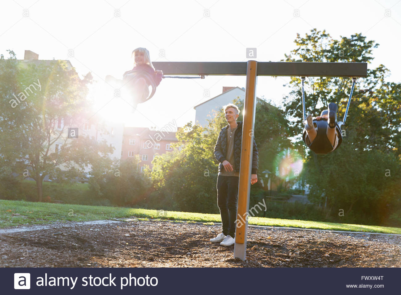 Sweden, Sodermanland, Arsta, Father with son (4-5) and daughter (2-3) swinging on playground at sunlight - Stock Image