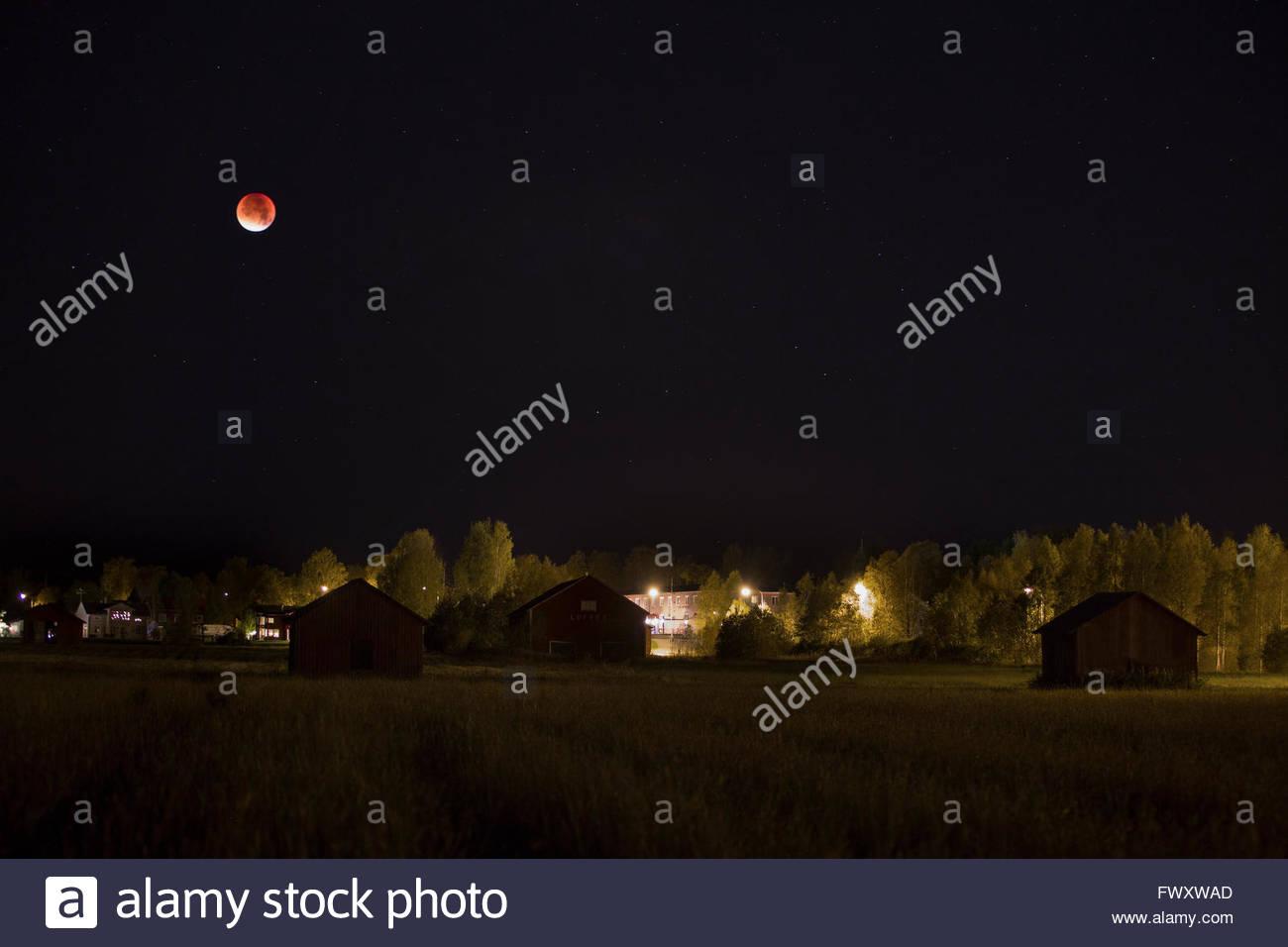 Sweden, Vasterbotten, Umea, Moon over residential district - Stock Image