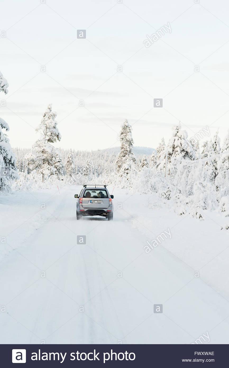 Sweden, Lapland, Gallivare, Car on road in winter - Stock Image