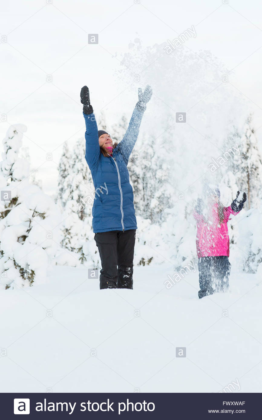 Sweden, Lapland, Gallivare, Girl (4-5) throwing snow with mother - Stock Image
