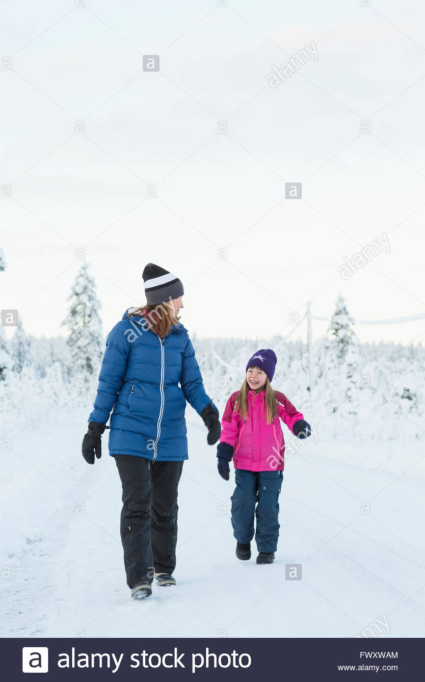 Sweden, Lapland, Gallivare, Girl (4-5) walking with mother along road in winter Stock Photo