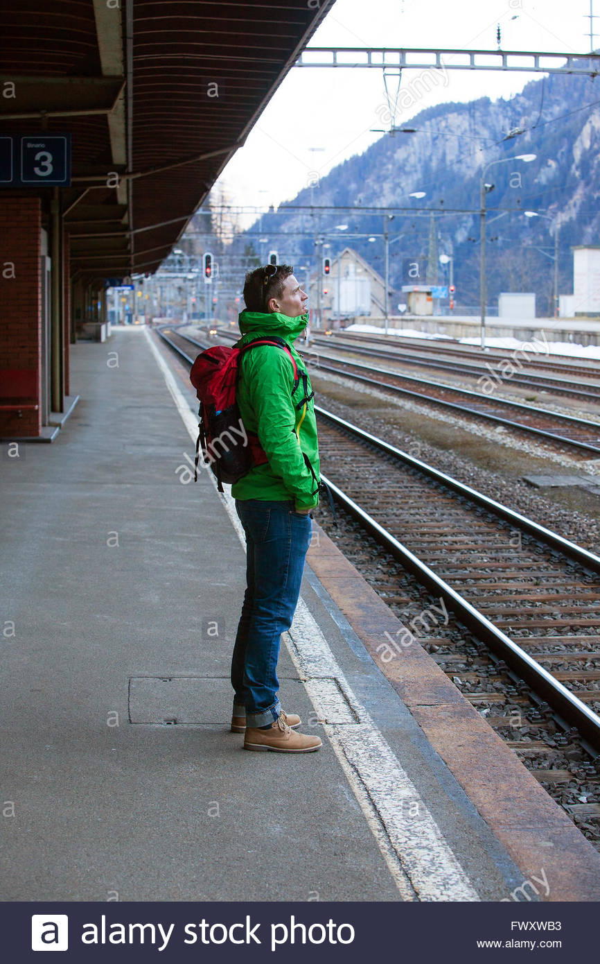 Switzerland, Andermatt, Mild adult man standing on railroad station platform - Stock Image