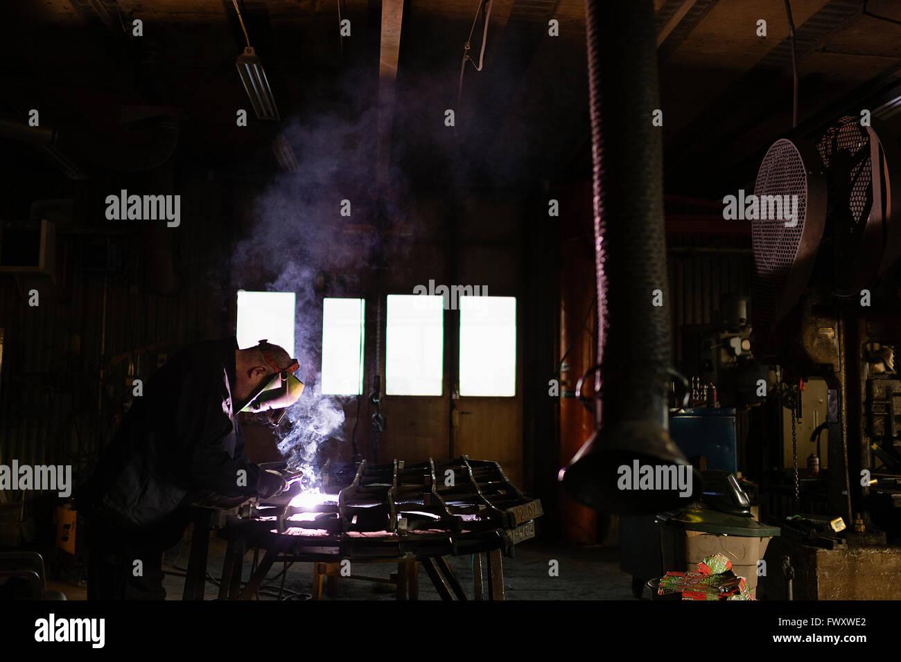 Sweden, Mature man welding construction frame - Stock Image