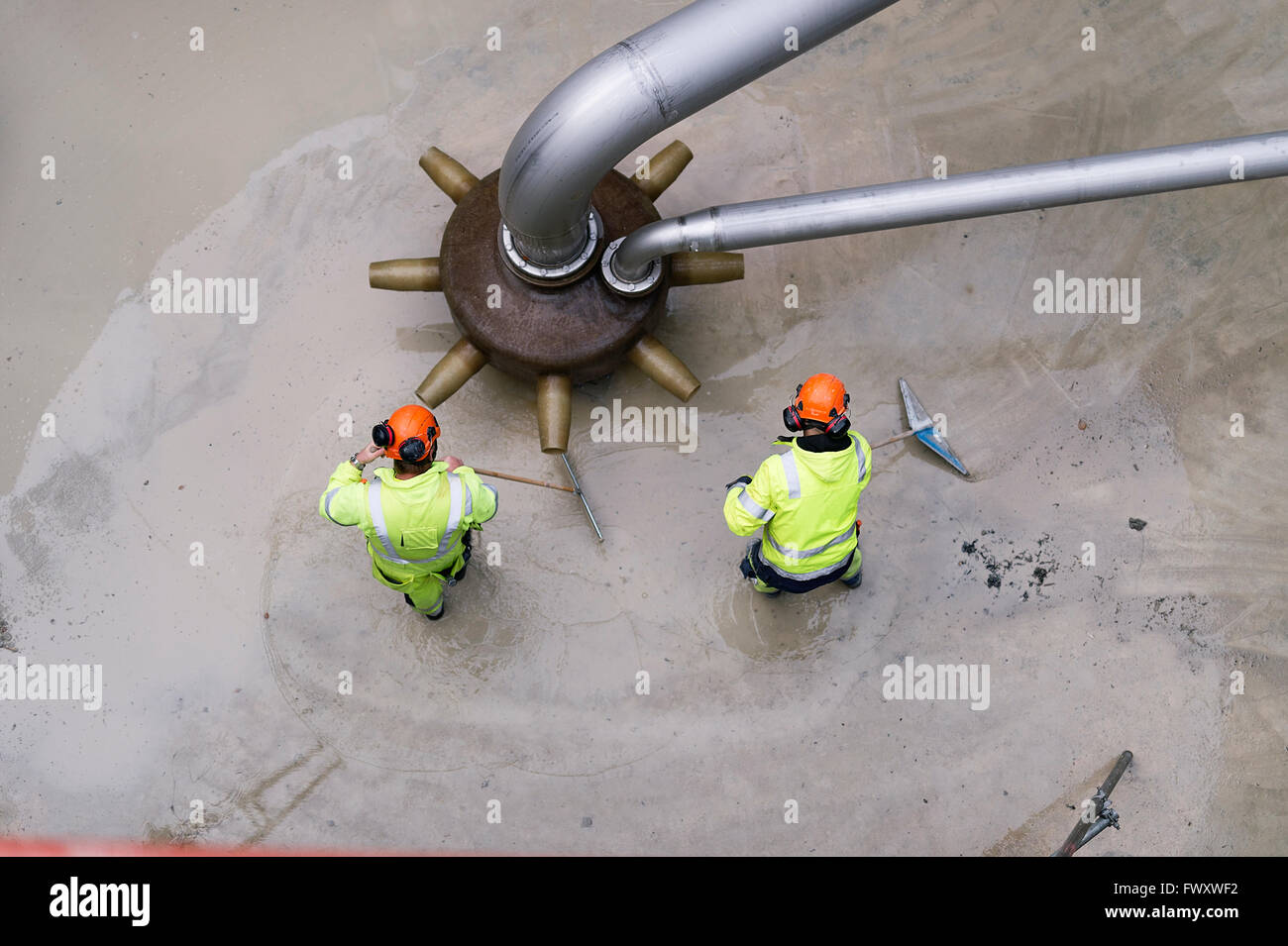 Sweden, Vastmanland, Two men working at water treatment plant - Stock Image