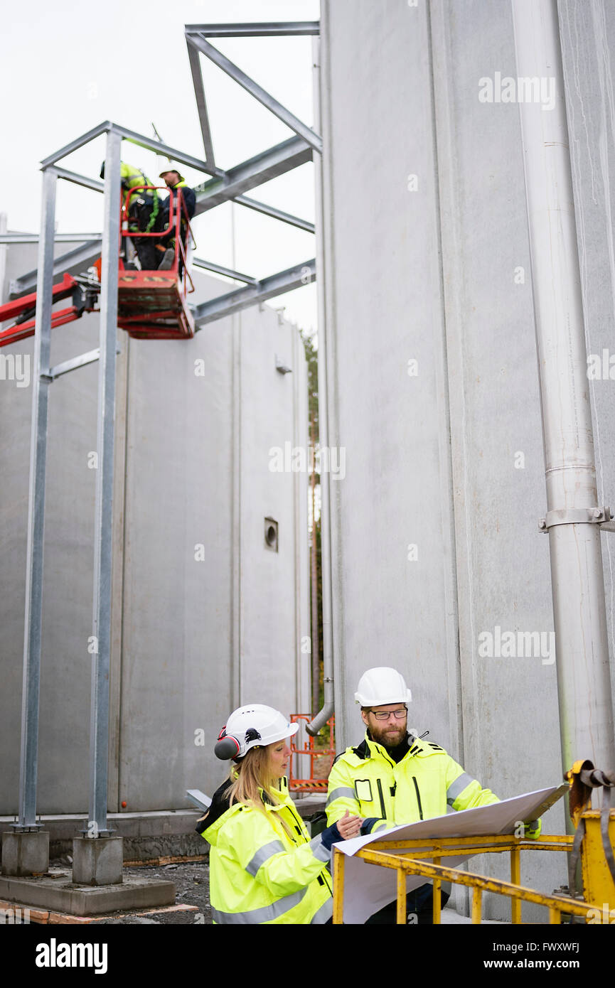 Sweden, Vastmanland, Four people working at water treatment plant - Stock Image