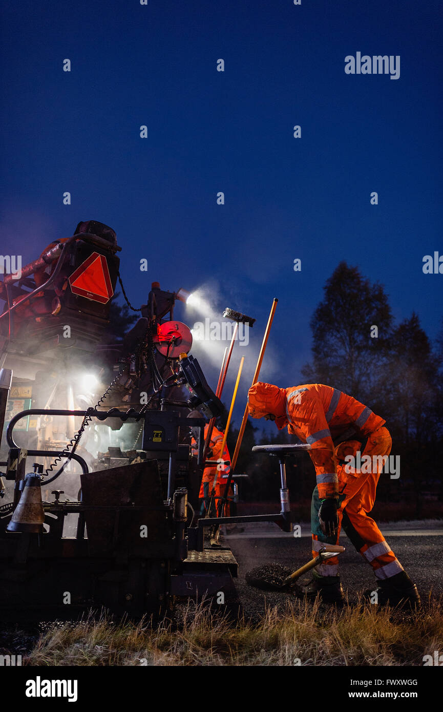 Sweden, Narke, Two manual workers repairing road at night - Stock Image