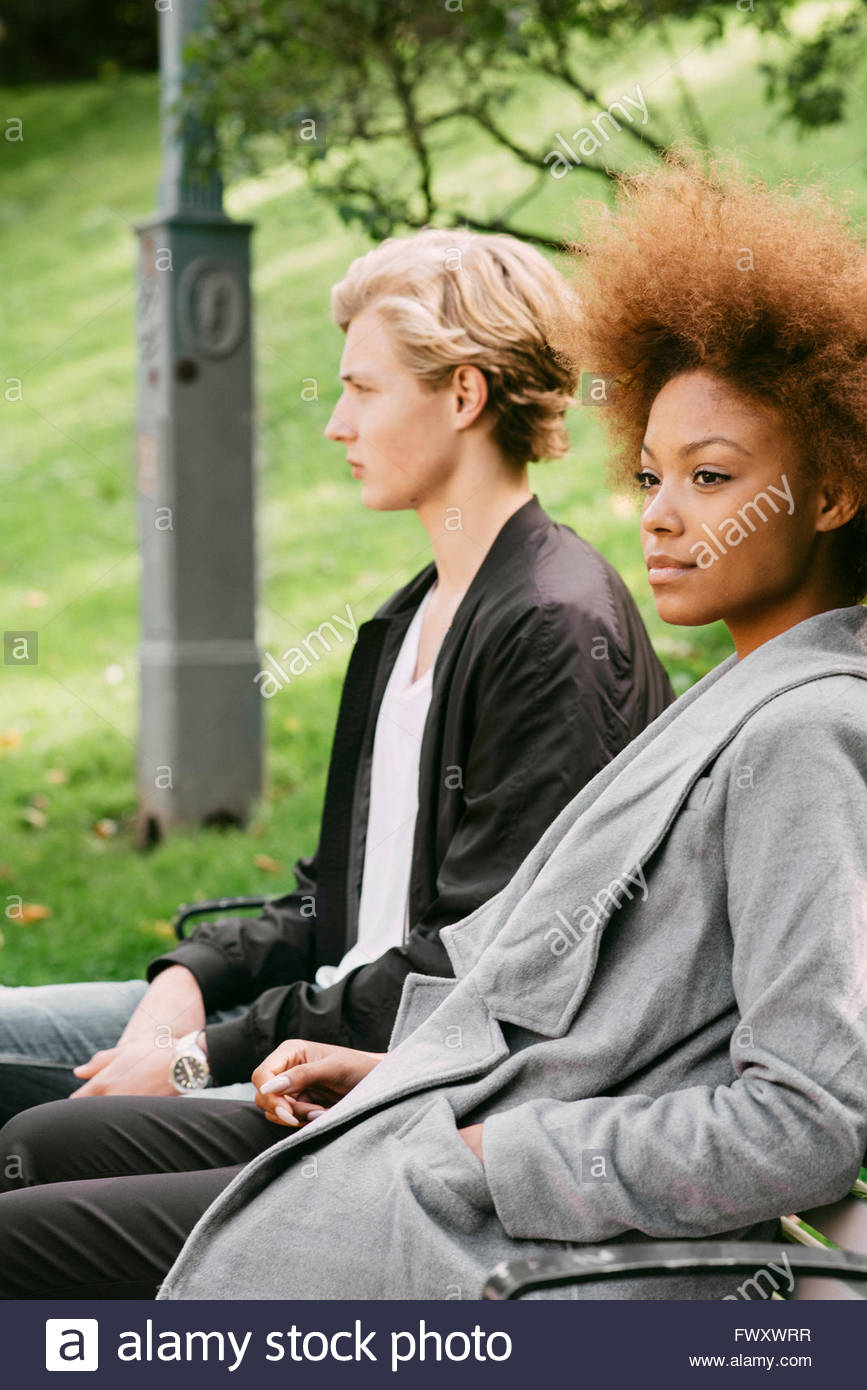 Sweden, Vastra Gotaland, Young couple sitting on bench in park Stock Photo