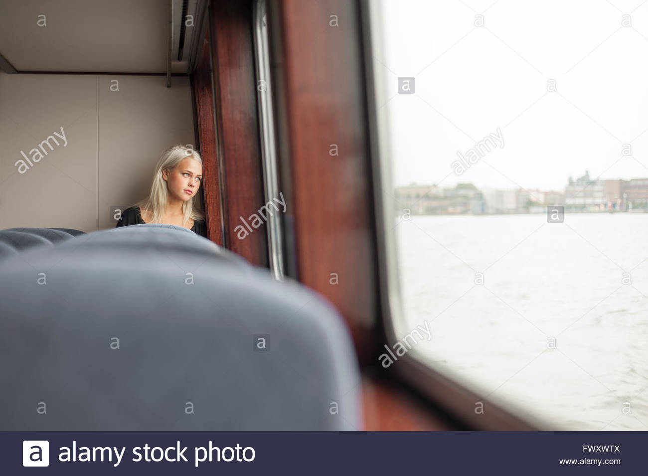 Sweden, Vastra Gotaland, Gothenburg, Young woman looking through window in train - Stock Image